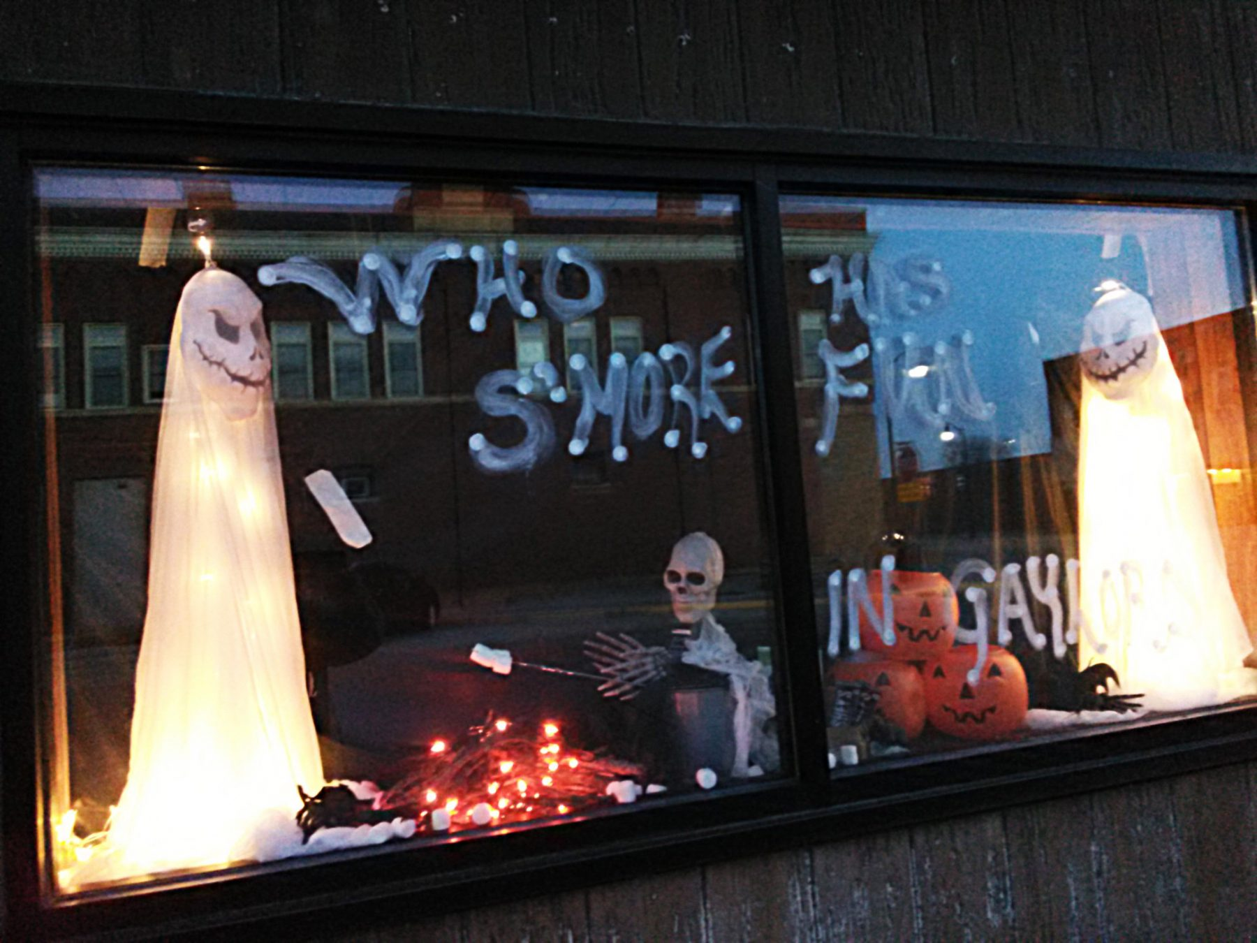 A store windows decorated for Halloween. A ghost and skeleton are having a campfire. The caption on the windows is Who has more fun in Gaylord